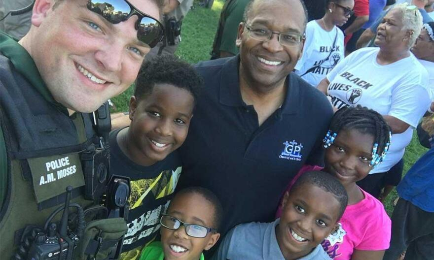 A Wichita police officer poses with residents at the First Steps Community Cookout on Sunday.
