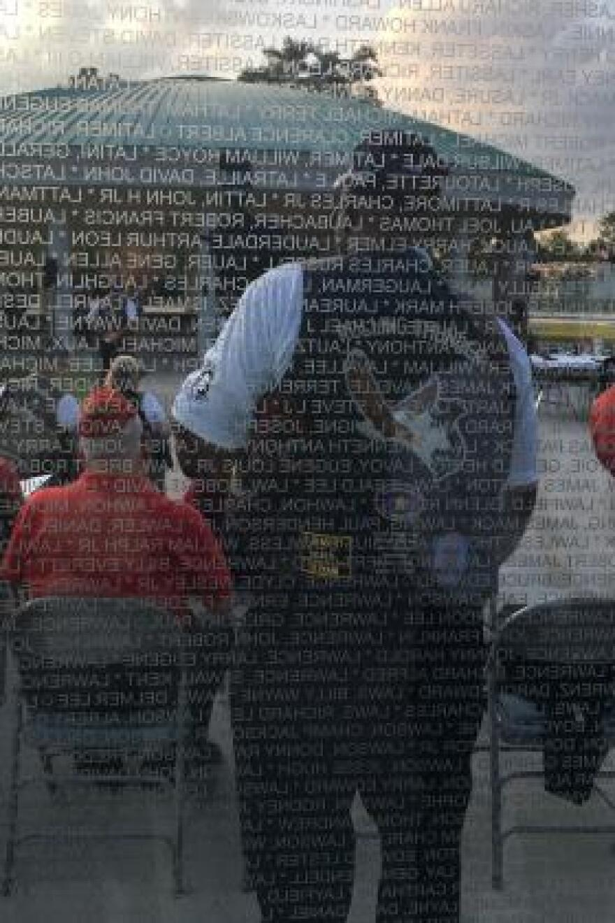 "Participants in a ""Rolling Thunder"" POW/MIA ceremony are reflected in a Vietnam War memorial at Lejeune Memorial Gardens in Jacksonville, N.C."