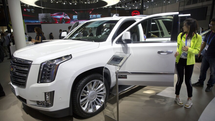 Visitors look at a Cadillac Escalade at the China Auto Show in Beijing in 2018. For General Motors, China is a bigger market than the United States.
