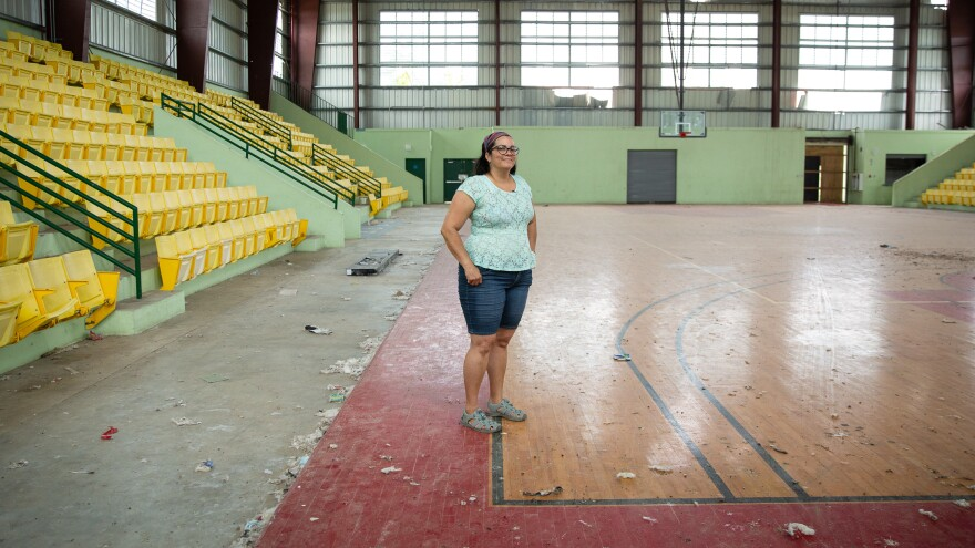 Elda Guadalupe Carrasquillo, a municipal legislator and a middle school science teacher in Vieques, Puerto Rico, stands on the island's only wooden basketball court. It was wrecked during Hurricane Maria. Since then, it's only been used by birds and roaming horses.