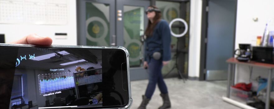 A photo of Caitlyn Lenhoff, a masters student in computer science at Kent State University, demonstrating how to use the team's helmet based augmented reality system.