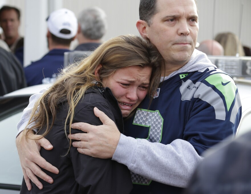 People react as they wait at a church on Friday where students were taken to be reunited with parents following a shooting at Marysville Pilchuck High School in Marysville, Wash.