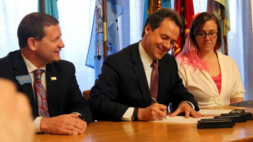 Gov. Steve Bullock signs the Medicaid expansion bill sponsored by Republican Sen. Ed Buttrey, left
