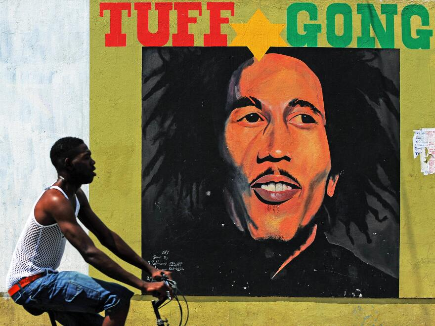 A man pedals past a mural of late musician Bob Marley in Kingston, Jamaica in 2009.