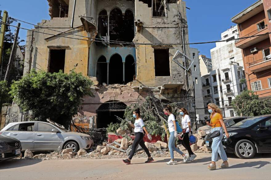 Women walk past a damaged building Wednesday in the aftermath of the blast that tore through Lebanon's capital. Rescuers continue to search for the missing.