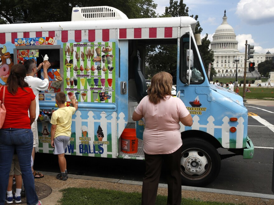 With the U.S. Capitol as a backdrop, tourists wait in line to get ice cream from a food truck on the National Mall in Washington.