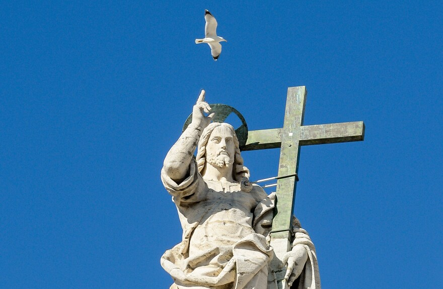 """A seagull flies over a statue of Jesus on the top of St. Peter""""s Basilica in Rome."""