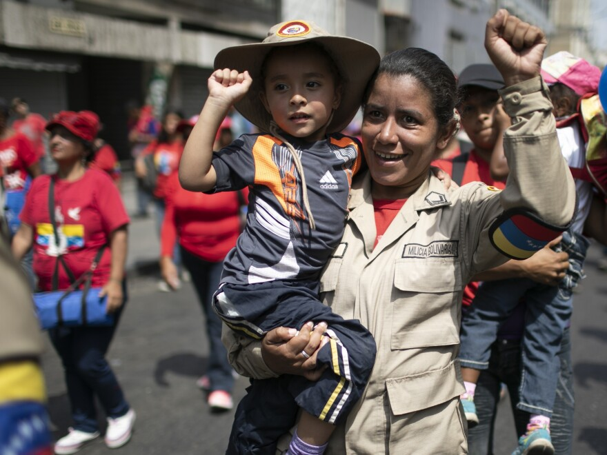 A woman of the National Bolivarian Militia carries her daughter during a pro-government march on International Women's Day in Caracas, Venezuela Sunday.