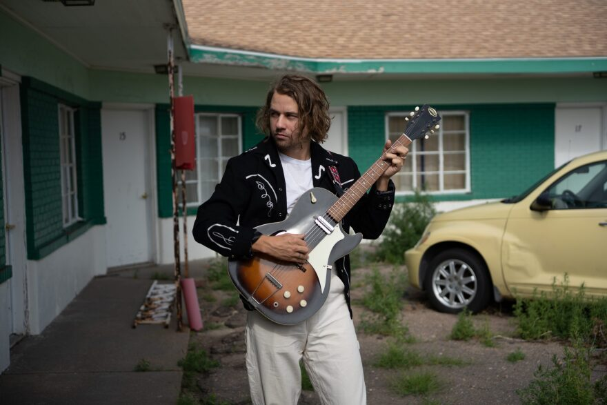Kevin Morby holding his guitar in front of a motel.