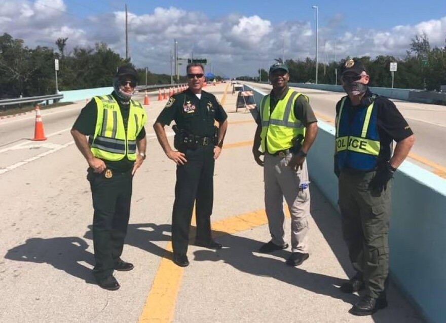 Monroe Sheriff Rick Ramsay, second from left, checks out the checkpoint at the Monroe County line on the 18 Mile Stretch Monday.