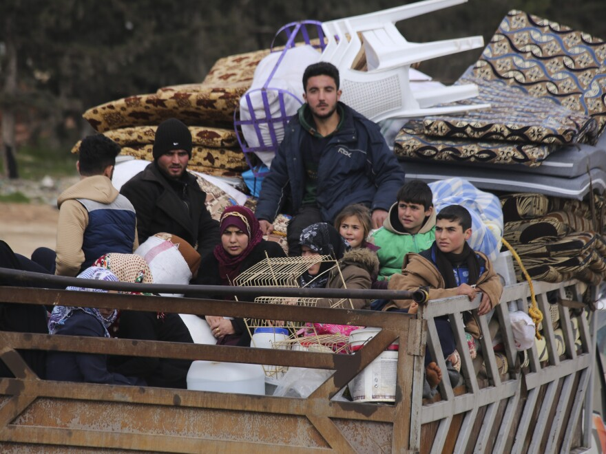 Syrian refugees head northwest through the town of Hazano in Idlib province as the flee renewed fighting Monday, Jan. 27, 2020. (AP Photo/Ghaith Alsayed)