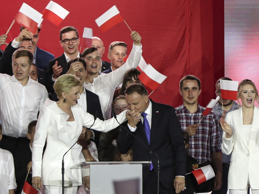 President Andrzej Duda kisses the hand of his wife, Agata Kornhauser-Duda, in Pultusk, Poland, on Sunday night. Duda won reelection by a narrow margin.