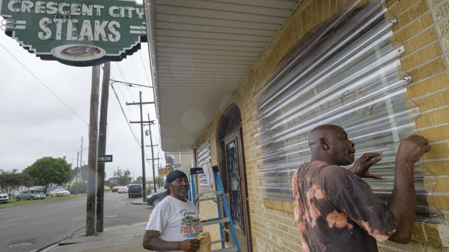 Crescent City Steaks chef Frank Turner (left) and dishwasher Keith Brooks screw in storm barriers over the restaurant's windows on Friday as Tropical Storm Barry approaches.