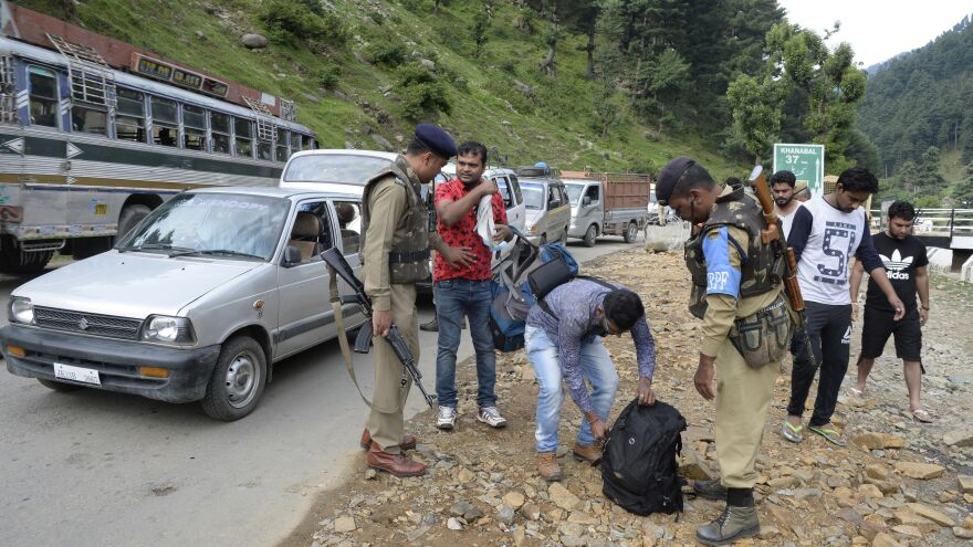 Indian paramilitary troopers search the bags of Hindu pilgrims during the annual pilgrimage to the shrine at Amarnath cave on Tuesday. Security forces protect the pilgrims, but police say the bus that was attacked was not authorized and thus not protected.