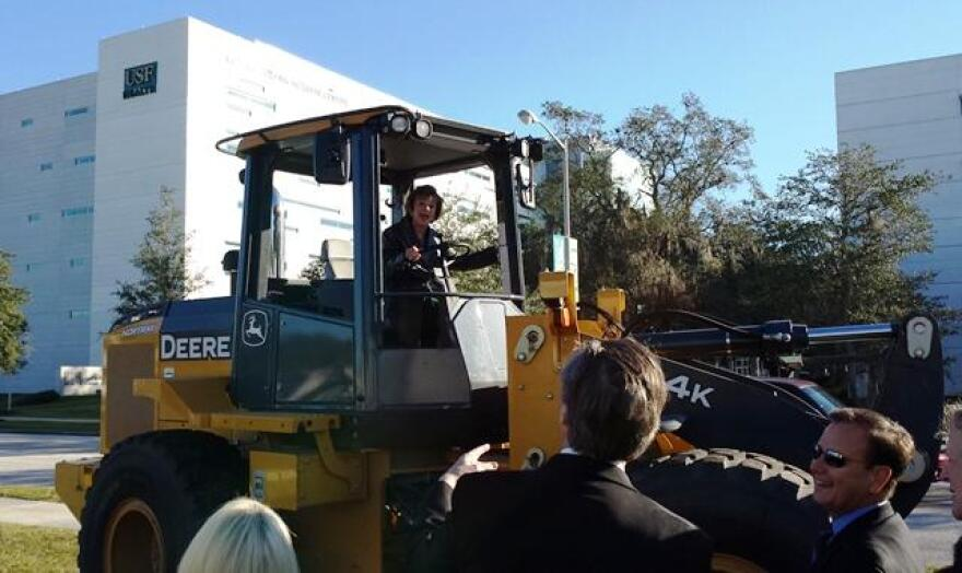 Judy Genshaft takes the controls of some of the construction equipment at the groundbreaking for the USF Heart Health Institute on the Tampa campus in Dec. 2013.