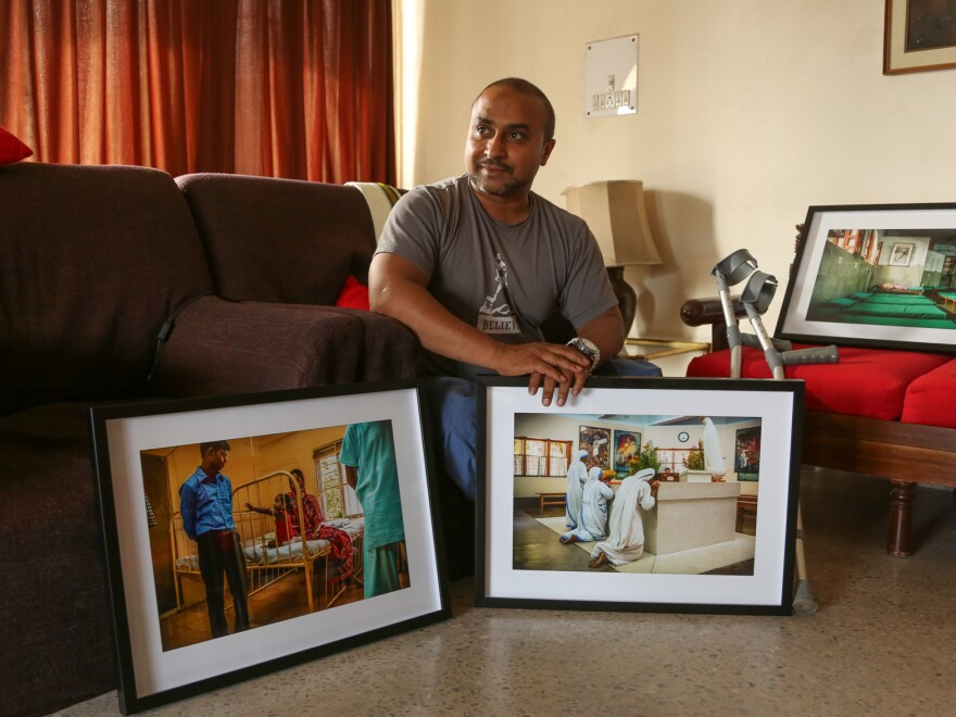 """Gautam Lewis, now 39, poses with some of the photographs he has taken that trace the life and work of Mother Teresa, who took him in when he was 3. The images are part of an exhibition Lewis has staged in Kolkata as an homage to the woman he calls his """"second mother."""""""