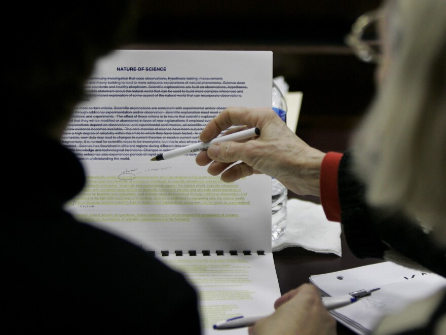 Kansas Board of Education members look over language for a science textbook in 2007. The fight over the teaching of evolution has been particularly fierce in Texas, which because of its size influences many textbook publishers.