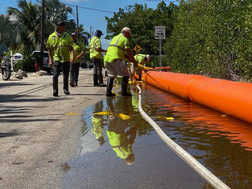workers install a flood barrier along a street in Key Largo's stillwright point neighborhood