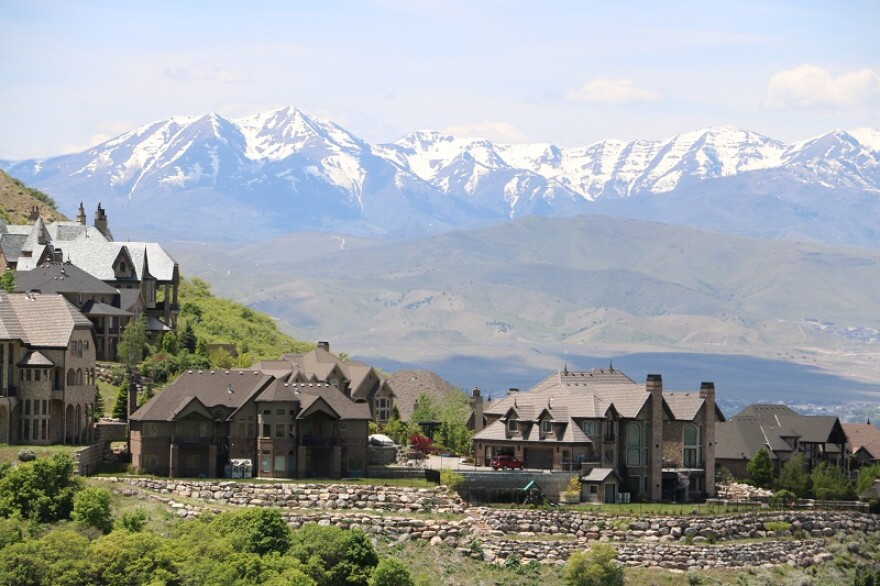 Large homes sit in the foothills, with snowy mountain peaks in the background.