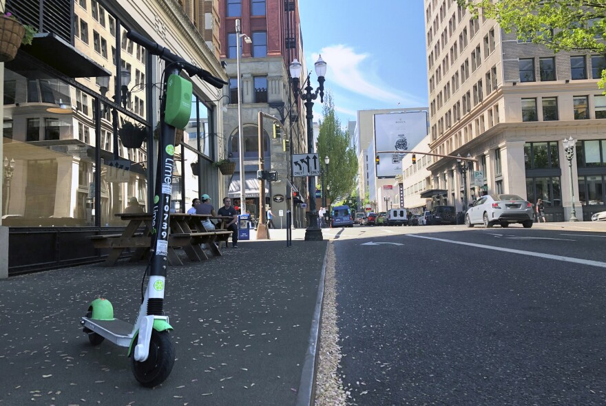 A lime e-scooter sits parked on a street in downtown Portland, Ore.