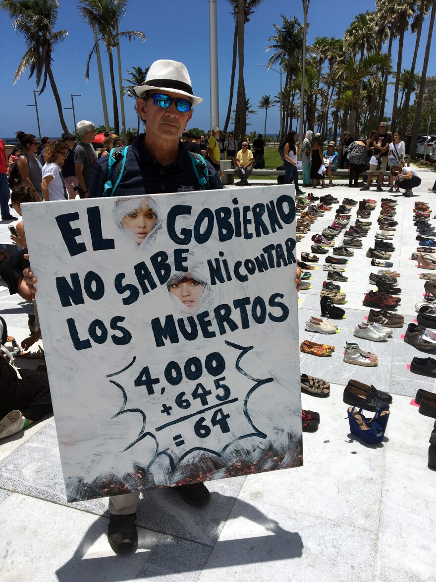 """""""The government doesn't even know how to count the dead,"""" this man's placard reads."""