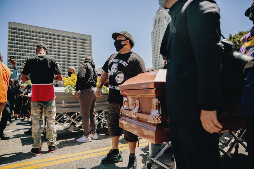 Johnson (center) helps put on a march Monday to honor black lives lost to police brutality. The group displayed caskets in memory of George Floyd and Breonna Taylor in downtown Los Angeles.