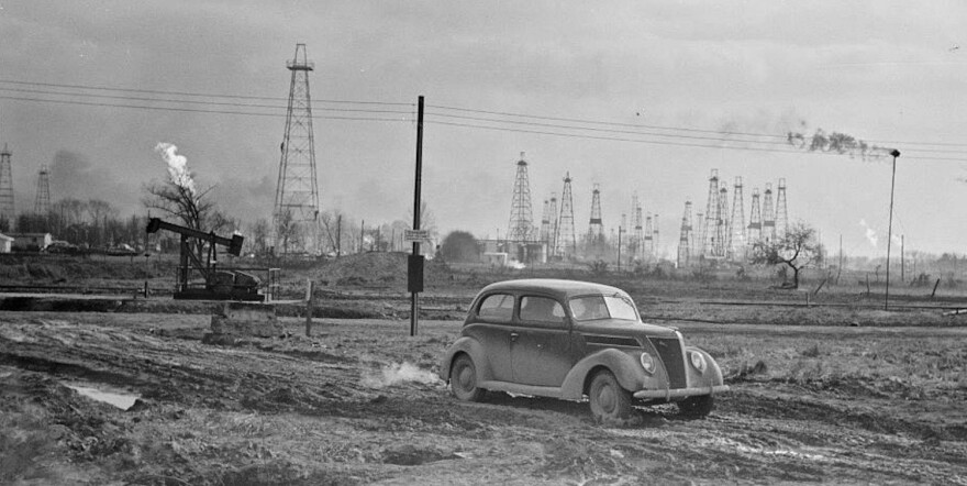 classic car in front of oil field in black and white