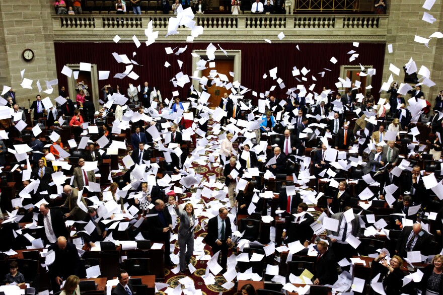 Members of the Missouri House of Representatives throw their papers in the air to mark the end of the legislative session on Friday in Jefferson City.