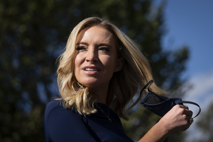 White House press secretary Kayleigh McEnany takes off her face covering before speaking with reporters outside the West Wing of the White House on Friday, the day President Trump announced he had tested positive for the virus.