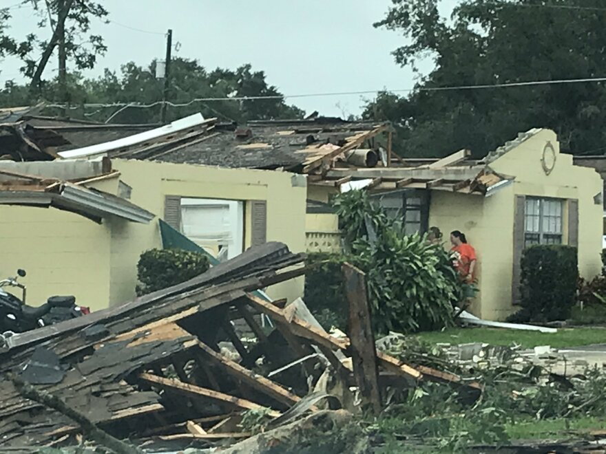 house damaged by tornado, with debris in front of house