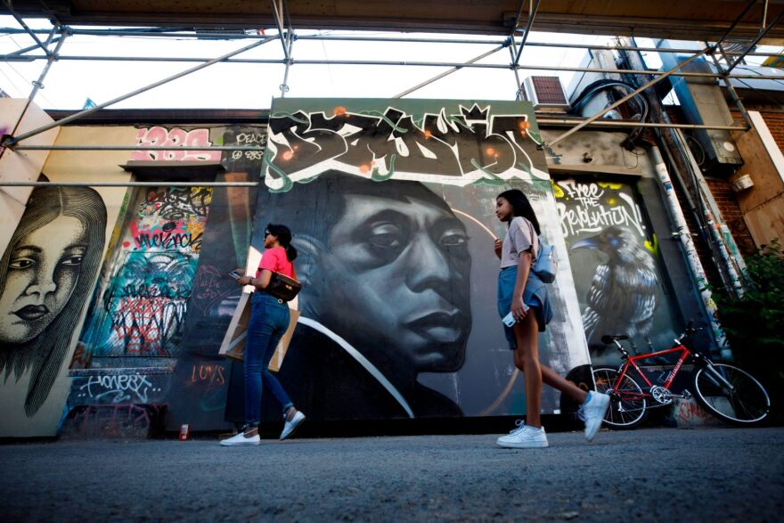 People walk by a mural of late American novelist and activist James Baldwin (C) in Toronto, Canada.