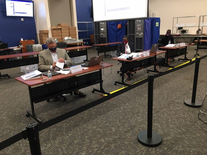 Three members of the canvassing board wear masks and sit at separate tables with stacks of ballots.