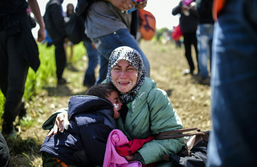 A woman and her children cry after being affected by tear gas near Idomeni on Sunday. Hundreds of people were hurt when police fired tear gas on a group of migrants as they tried to break through a fence on the Greece-Macedonia border, Doctors Without Borders said.