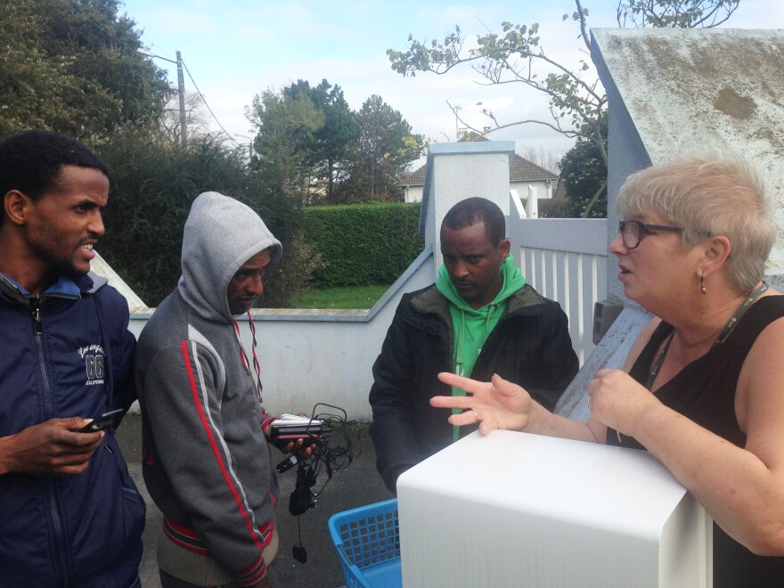 Migrant men talk to Calais resident Brigitte Lips, who lets them charge their cellphones — their only lifelines to families left behind — at her home.
