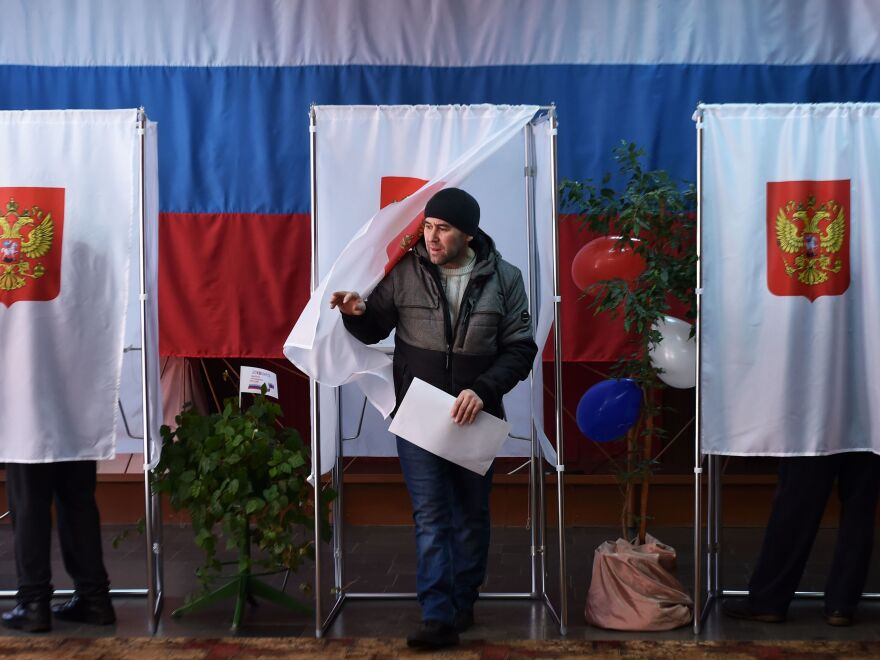 A man walks out of a voting booth at a polling station during Russia's presidential election in the village of Novye Bateki.