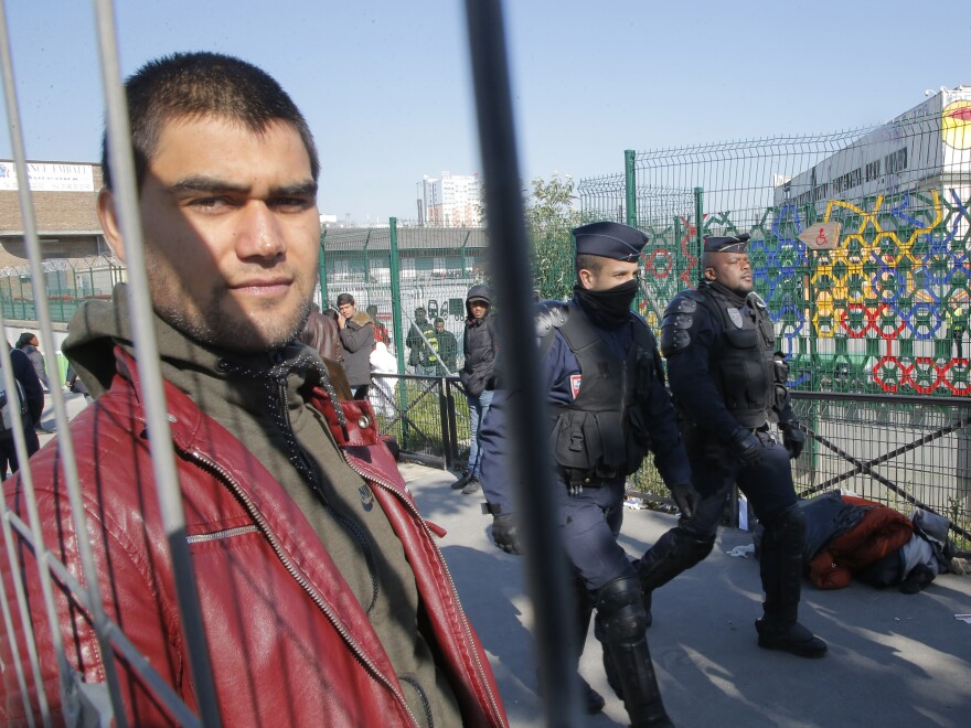 A young man looks on as police officers pace a makeshift camp they evacuated Tuesday.