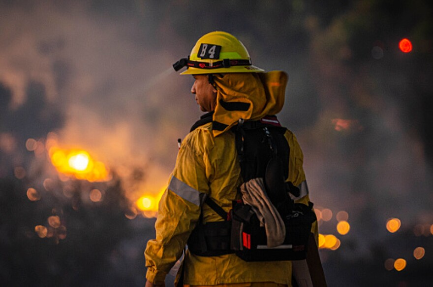 A photo of a firefighter looking at a fire in Los Angeles, California.