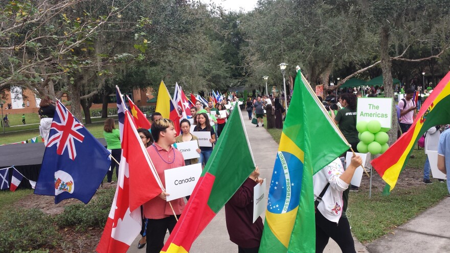 Students marching, holding flags of their home countries.