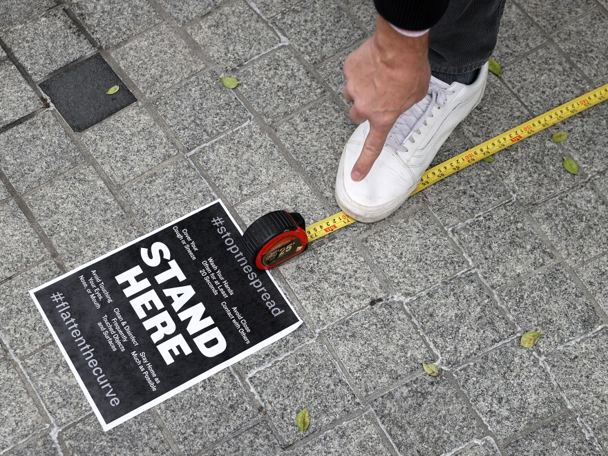 Workers use a tape measure mark spaces six feet apart for people to wait in line safely as they convert the outdoor plaza in front of Zaytinya, one of Chef José Andres' restaurants in Washington, D.C. Efforts to contain the coronavirus are affecting blood donor drives and supplies.