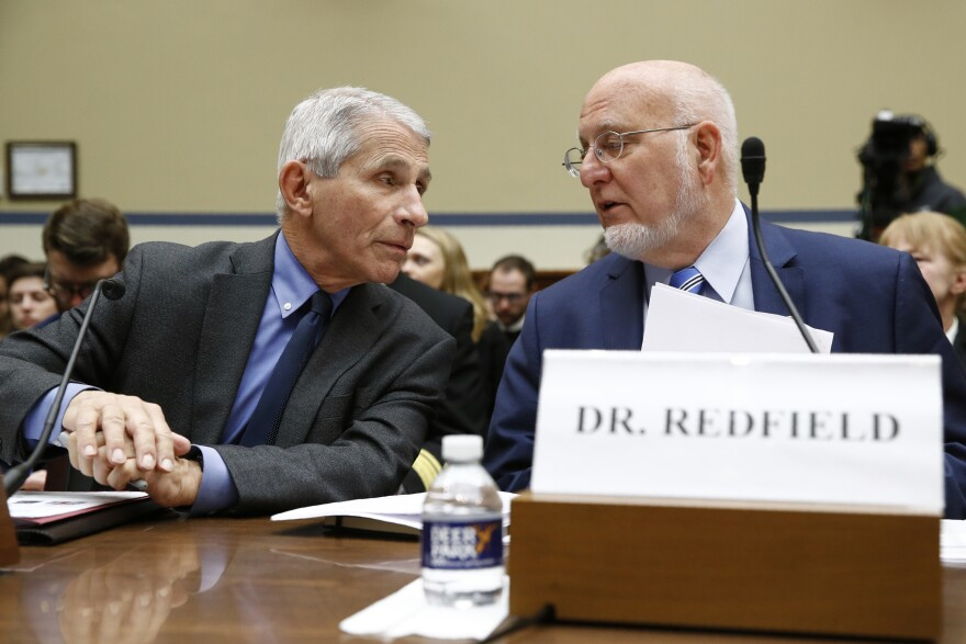 Dr. Anthony Fauci (left), director of the National Institute of Allergy and Infectious Diseases, confers with Dr. Robert Redfield, director of the Centers for Disease Control and Prevention, at a congressional hearing on March 11.