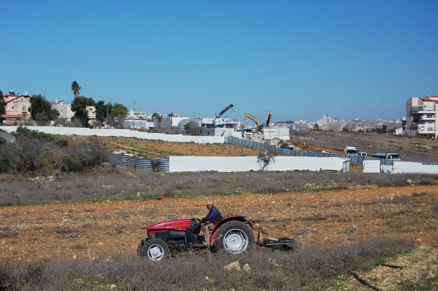 A Palestinian farmer from the nearby village of Jib got an Israeli permit to cross a military checkpoint and prepare his land next to the settlement of Giv'at Ze'ev for sowing wheat. The disputed synagogue is being dismantled in the background as he works.