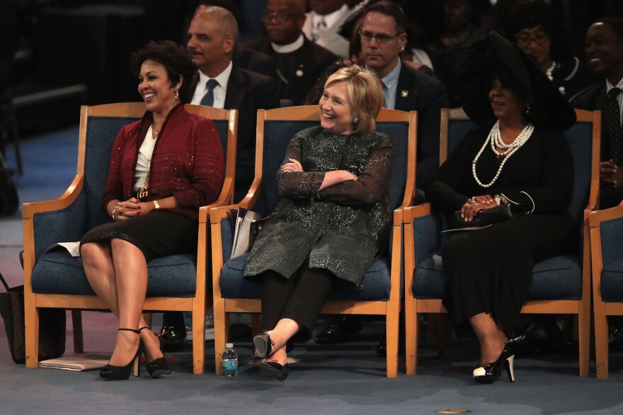 """Former Secretary of State Hillary Clinton listens while her husband speaks. Before holding their many political offices, Bill Clinton said, the couple considered themselves """"Aretha groupies."""""""