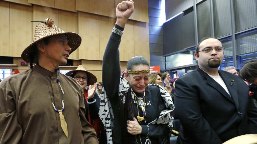 Olivia One Feather (center) of the Standing Rock Sioux tribe holds up her fist after the Seattle City Council voted Tuesday to divest from Wells Fargo over its role as a lender to the Dakota Access Pipeline project.