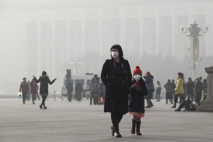 A foreign tourist and a child wearing protection masks walk through Tiananmen Square in Beijing as the city was blanketed by heavy smog last week.