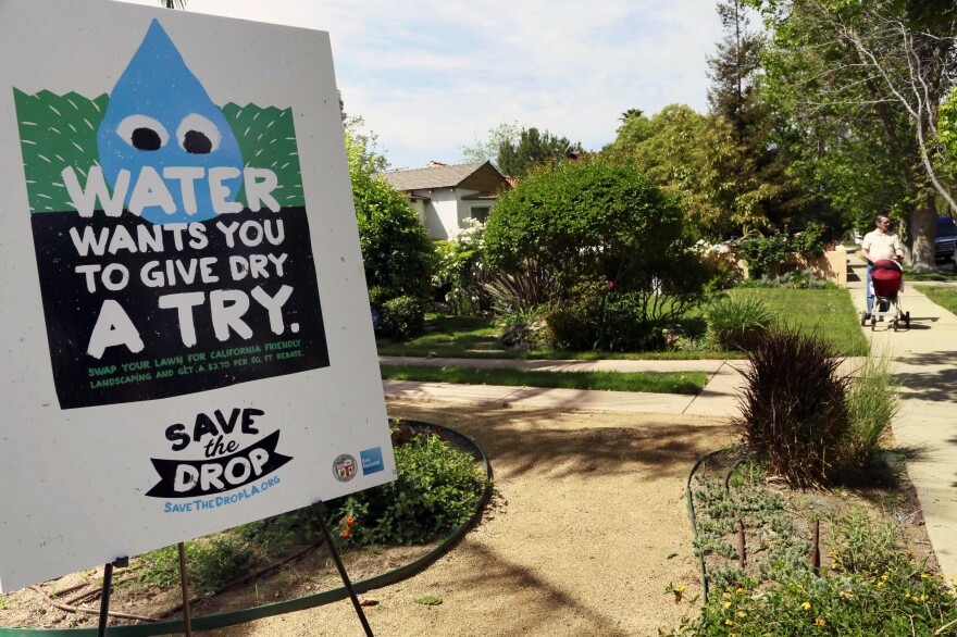"""A sign encouraging people to save water is displayed at a news conference in Los Angeles. Water use restrictions in California amidst the state's ongoing drought have led to the phenomenon of """"droughtshaming,"""" or publicly calling out water wasters."""