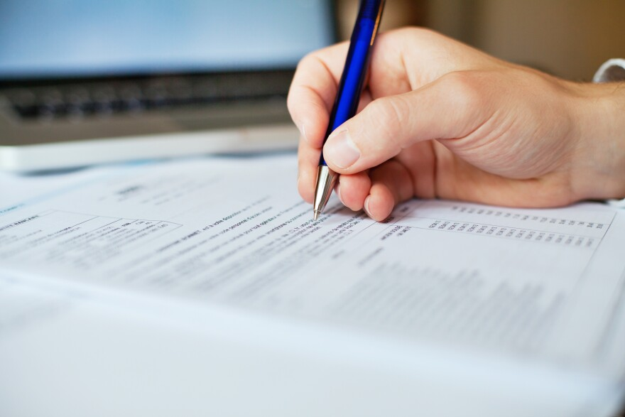 Photo illustration of filling out tax forms.