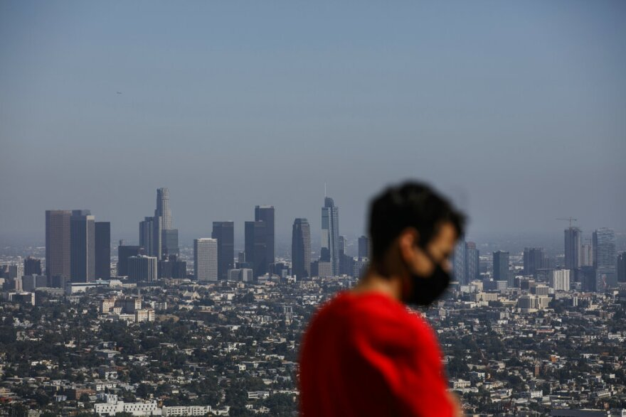 Izzy Galvan, 20, wears a face mask while visiting the Griffith Observatory overlooking downtown Los Angeles, Wednesday, July 15, 2020, in Los Angeles.  (AP Photo/Jae C. Hong)