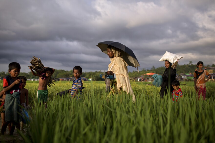 Rohingya women and children walk through a refugee camp outside of Cox's Bazar, Bangladesh, where nearly one million people have taken refuge, many with visible wounds and scars from human rights abuses committed against them in Myanmar.