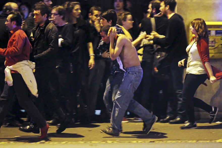 An injured man holds his head as people gather near the Bataclan concert hall.