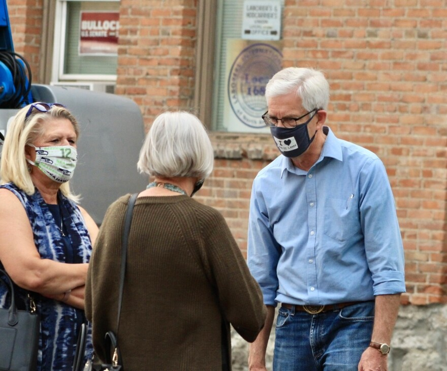 """Montana Lt. Gov. Mike Cooney speaks from a distance with a woman outside. He wears a blue cloth face mask that reads """"I [heart] public lands"""" over the shape of the state of Montana."""